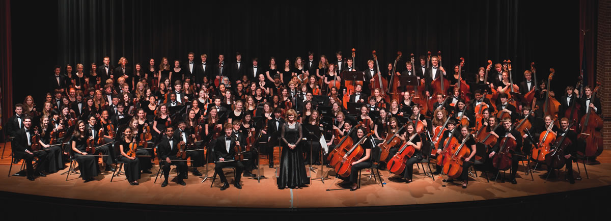 The Charlottesville High School Orchestra poses on stage for a group portrait