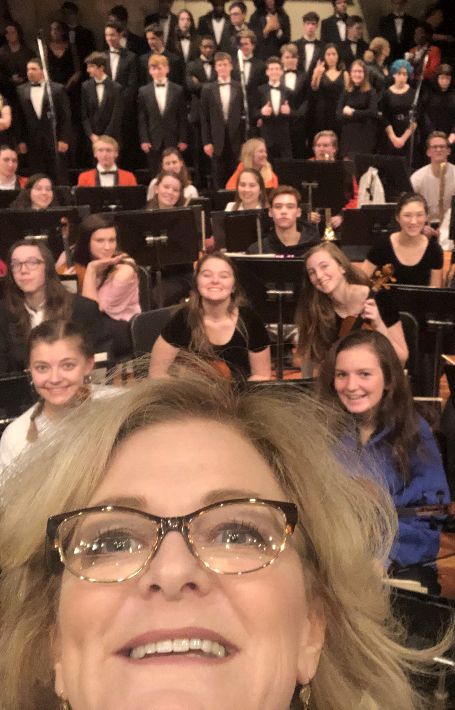 Director Laura Mulligan Thomas appears in the foreground as she takes a 'selfie' style photo of the orchestra