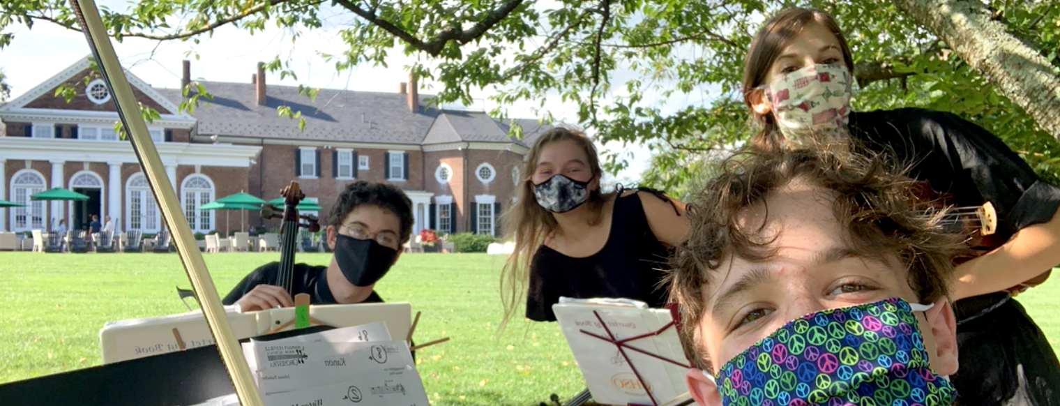 Four students wearing masks pose for the camera holding their instruments in front of a Jeffersonian style building