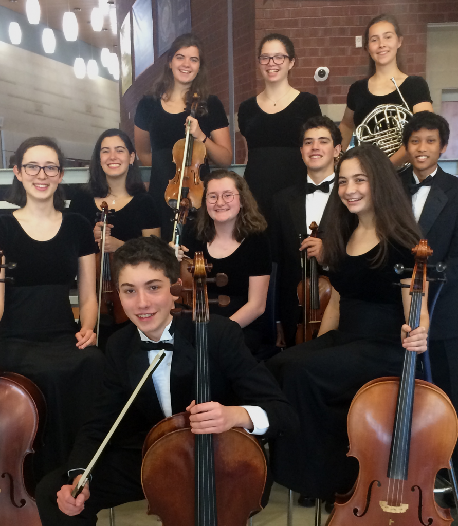 Ten students in formalwear pose with their instruments in the halls of a school